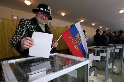 Frau mit Russlandfahne bei Stimmabgabe