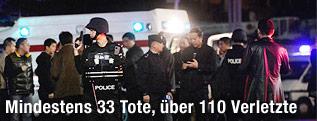 Polizist steht vor Rettungswagen