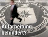 Ein Mann geht über ein CIA-Logo auf dem Boden