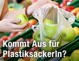 Eine Frau in der Obstabteilung gibt Äpfel in ein Plastiksackerl