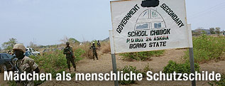 Soldaten und Schild einer Schule in Chibok, Nigeria