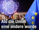 Personen neben einer EU-Flagge blicken auf ein Feuerwerk