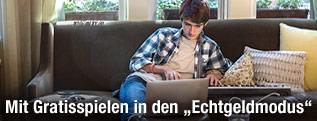 Junger Mann hinter Laptop