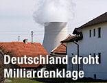 Kühlturm des AKWs Isar 1 und 2 hinter Häusern eines bayrischen Dorfes