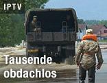 Militärlastwagen fährt auf überfluteter Straße