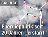Windräder vor dem Rauch eines Kraftwerkkühlturms