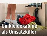 Beine einer weiblichen Person neben Kleidungsstücken in einer Umkleidekabine