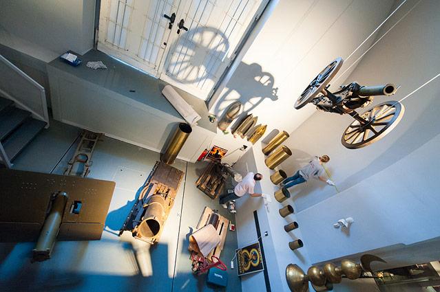 Kanone von der Decke hängend und Museumspersonal beim Aufhängen von Exponaten