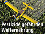 Flugzeug versprüht Pestizide über Feld