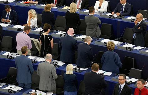 Abgeordnete des Europaparlaments stehen mit dem Rücken zum Podium