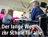 Kind im Rollstuhl sitzt in einer Schulklasse