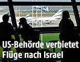 Umrisse von Personen mit Blick auf das Rollfeld des Flughafens von Tel Aviv