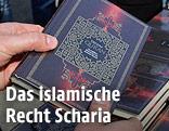 Eine Person hält eine Ausgabe des Koran in den Händen