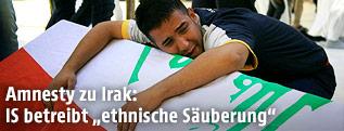 Ein Iraker ist über einen Sarg gebeugt