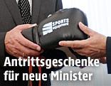 Michael Spindelegger überreicht dem neuen Finanzminister Hans Jörg Schelling (ÖVP) schwarze Boxhandschuhe