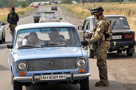 Ein ukrainischer Soldat kontrolliert ein Fahrzeug