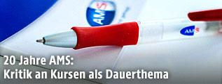 Kugelschreiber mit AMS-Logo auf AMS-Folder