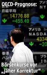 Mann vor elekronischer Tafel mit Aktien-Indizes verschiedener Länder