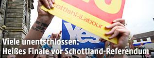 Befürworter und Gegner einer Abspaltung Schottlands halten Tafeln in die Höhe
