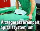Mediziner schiebt in einem Spital ein Krankenbett zur Seite