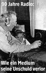 Mann sitzt mit einem Buben vor dem Radiogerät