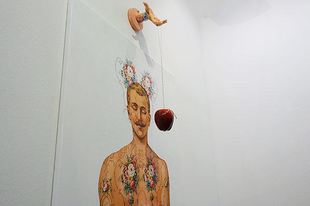 Hand hält einen Apfel an einer Schnur vor einem mit Blumen geschmückten Mann