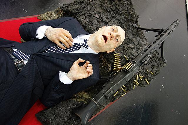 Mann im Anzug liegt neben einem Maschinengewehr