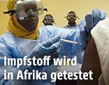 Person in Schutzanzügen gibt eine Impfung
