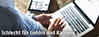 Person arbeitet gleichzeit mit Laptop und Tablet