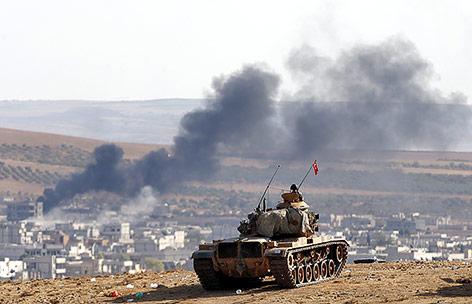 Türkischer Panzer steht auf einem Hügel mit Blick auf eine Rauchsäule in der syrischen Stadt Kobane