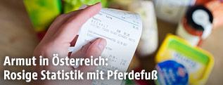Hand hält Supermarktrechnung
