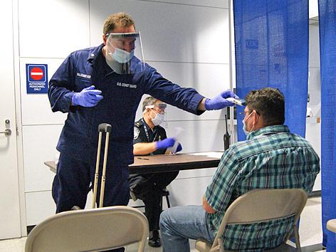 Ein Mann mit Schutzmaske misst am Flughafen bei einem Passagier die Temperatur