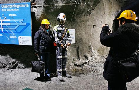 Person lässt sich mit einer Minenarbeiter-Puppe in Kiruna fotofagrafieren