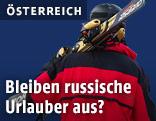 Skiurlauber trägt seine Skier auf der Schulter