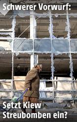 Frau geht an einem zerstörten Gebäude vorbei