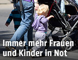 Frau mit Kind und Kinderwagen