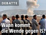 Menschen blicken von der Türkei aus auf die Stadt Kobane