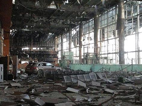 Auto in einer zerstörten Flughafenhalle