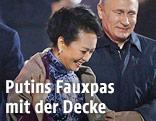 Russlands Präsident Vladimir Putin legt eine Decke um die Ehefrau des chinesischen Präsidenten