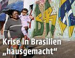 Frau mit Kind auf einer Straße mit Graffiti im Hintergrund
