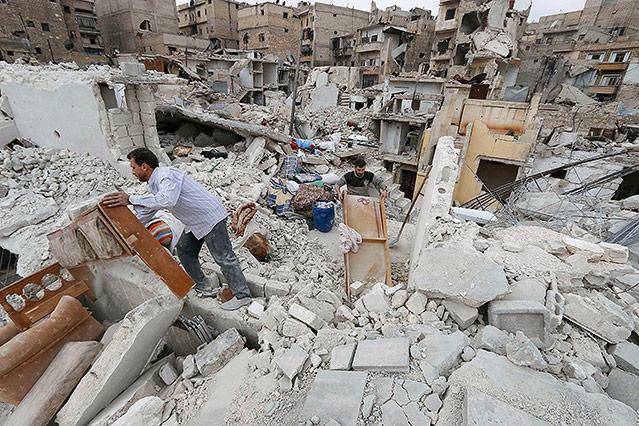 Menschen durchsuchen Trümmer in Aleppo