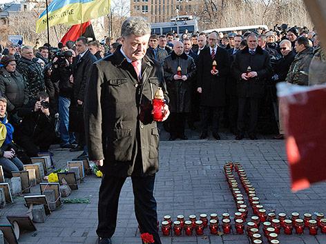 Ukraines Präsident Petro Poroschenko mit einer Grabkerze