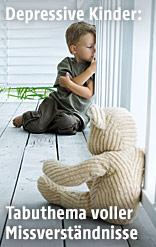 Kleiner Bub sitzt am Boden und schaut aus dem Fenster