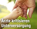 Hand eines Erwachsenen und eines Kindes