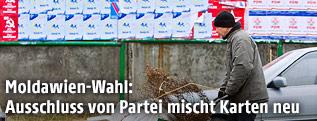 Mann mit Schubkarre passiert Wahlplakate in Chisinau, Moldawien