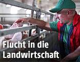Bauer streichelt seine Schweine
