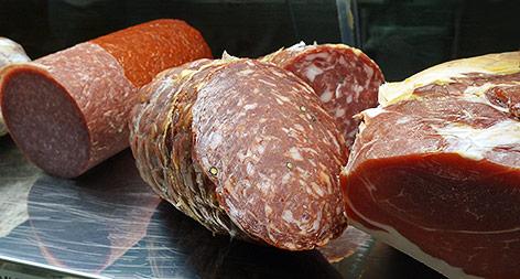 Salamiwurst neben einem Prosciuttoschinken