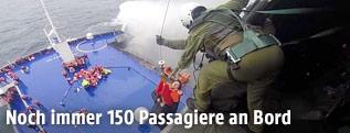Bergung von Passagieren durch ein Rettungsteam in einem Hubschrauber über der Fähre