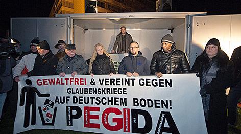 Demonstranten halten ein Pediga-Banner