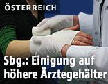 Ein Arzt verbindet eine Hand
